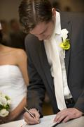 Civil ceremony, groom signing a marriage certificate at the registry office Stock Photos