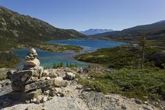 inukshuk on historic chilkoot pass, chilkoot trail, deep lake behind, yukon t - stock photo