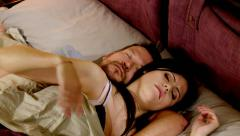 Couple disturbing each other during sleep in bed - stock footage