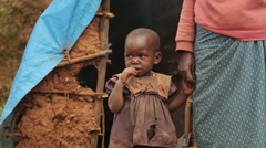 African Mother and Child from Batwa Tribe in Front of Their Hut, Uganda Arkistovideo