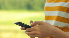 Close-up of girl using phone in nature, surfing the internet, camera movement - stock footage