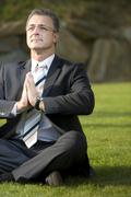 businessman doing a relaxation exercise in a park - stock photo