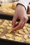 Stock Photo of woman putting cut-out cookie dough on a baking tray