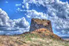 nuraghe under clouds - stock photo