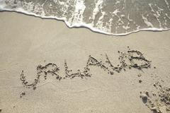 Urlaub, german for holiday, written in wet sand Stock Photos
