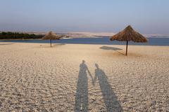 Shadow of couple on pebble beach in zrce bay, pag island, dalmatia, adriatic  Stock Photos
