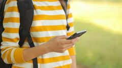 Young tourist using cell phone outdoors, online maps, nature, camera movement Stock Footage