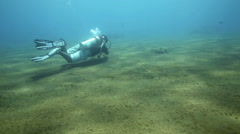 Scuba diver swimming over sandy ocean floor executing perfect neutral buoyancy Stock Footage