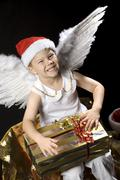 boy dressed as christmas angel with christmas present - stock photo