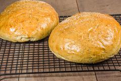 artisan rosemary bread on cooling rack - stock photo
