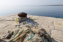 bollards and fishing net in the harbor in kosljun, pag island, dalmatia, adri - stock photo