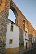 Homes in the arches of the medieval aqueduct, evora, unesco world heritage si Stock Photos