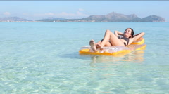Young woman on pool raft in the mediterranean sea, majorca Stock Footage