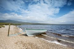fishing boat on the shore of loch loyal, sutherland, scotland, great britain, - stock photo