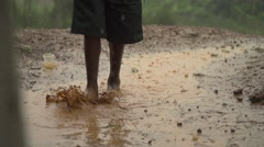 African Child from Batwa Tribe Playing with Feet in Muddy Water in Slow Motion - stock footage