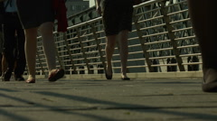 Crowd of pedestrians walk over Golden Jubilee Bridge, London. HD version Stock Footage