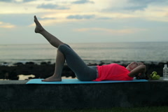 Young, pretty woman exercising sit-ups on the wall by the sea NTSC Stock Footage