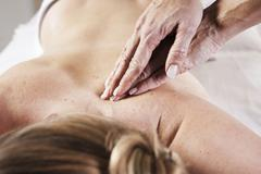 young woman being massaged on the back by a therapist - stock photo