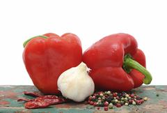 Two red capsicums, garlic and peppercorns Stock Photos