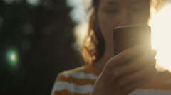 Young girl using cell phone outdoors in the evening, surfing the internet Stock Footage