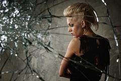 Punk girl behind broken glass Stock Photos