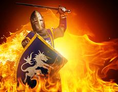medieval knight in attack position on fire background. - stock illustration
