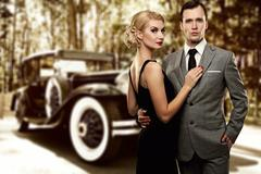 retro couple against old car. - stock photo