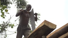 African Man Cutting Wood with Saw in Slow Motion, Uganda Stock Footage