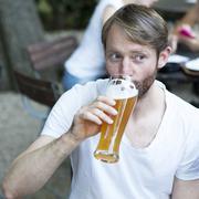 Mann drinking wheat beer in a beer garden Stock Photos