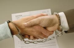 Handshake with tied hands, handcuffs, contract at back, symbolic image for ad Stock Photos