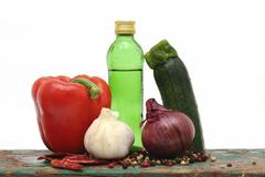 capsicum, zucchini, garlic, onion and a bottle of oil - stock photo
