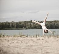 Young woman doing cartwheels on the beach Stock Photos