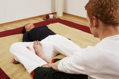 Young woman doing relaxation exercises with a qigong coach Stock Photos