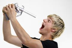 young man holding a petrol pump nozzle in front of his open mouth - stock photo