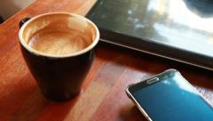 Putting a smart phone on the table with a cup of coffee and a note book Stock Footage