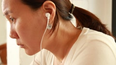 Asian woman with earphones studying hard Stock Footage