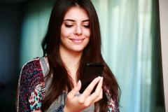 Happy woman using smartphone at home Stock Photos