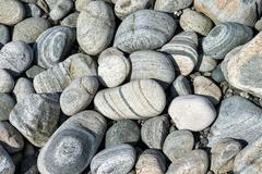 banded and round gneiss, on the gravel beach, geopark scourie bay, sutherland - stock photo