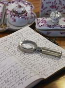 still life with a handwritten diary, magnifying glass and antique bone china  - stock photo