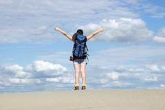 Girl hiker with thumbs up in desert Stock Photos
