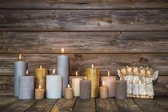 christmas greeting card with candles and angels on wooden background. - stock photo