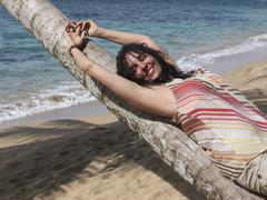 woman, 45, relaxing by lying on a palm tree, punta uva, puerto viejo de talam - stock photo