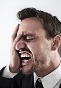 desperate young man wearing a suit covering his face with his hand, screaming - stock photo