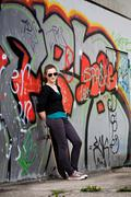 Teenage girl with skateboard standing in front of a graffiti wall, urban area Stock Photos