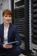 Stock Photo of Happy technician sitting on floor beside server tower using tablet pc