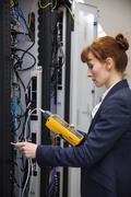 Technician using digital cable analyzer on server - stock photo