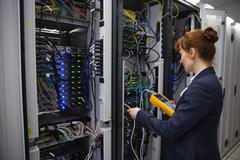 Happy technician using digital cable analyzer on server - stock photo