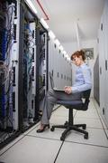 Technician sitting on swivel chair using laptop to diagnose servers - stock photo