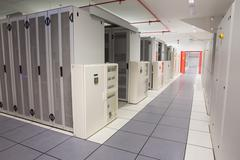 Empty hallway of server towers - stock photo