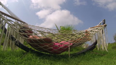 Man Relaxing In A Hammock On The Beach Stock Footage